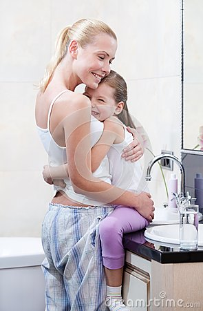 Mother and daughter embrace each other in bathroom