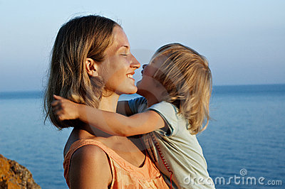 Mother and daughter embrace on seashore