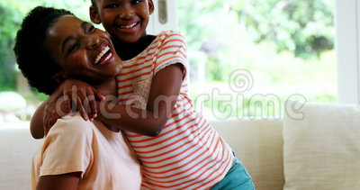 Mother and daughter embracing each other in living room. At home stock video