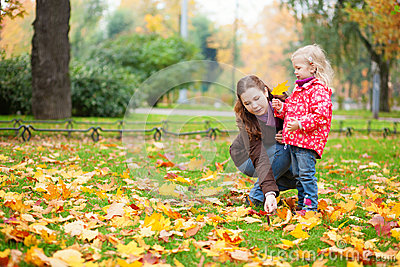 Mother and daughter gathering maple leaves