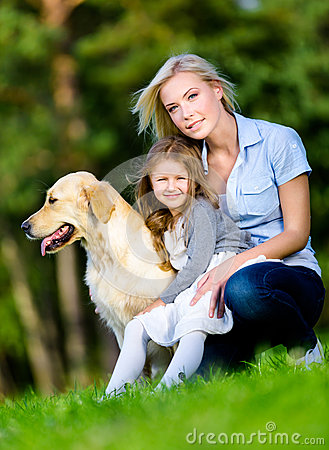 Mother and daughter with golden retriever are on the green grass