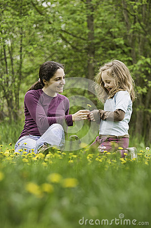 Mother and daughter in the grass with flowers