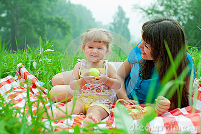 Mother and daughter have picnic eating apple