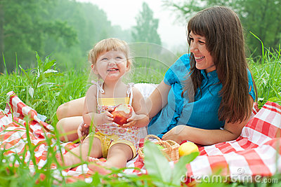 Mother and daughter have picnic eating apples
