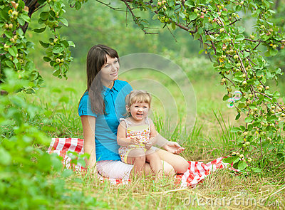 Mother and daughter have picnic outdoor