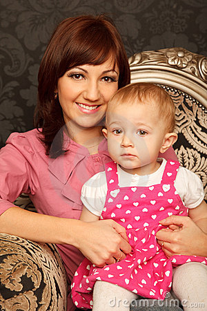 Mother and daughter on her lap sitting in armchair