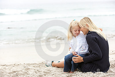 Mother And Daughter On Holiday Sitting On Beach