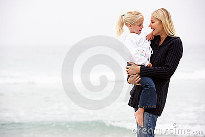 Mother And Daughter On Holiday Standing On Beach