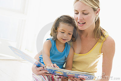 Mother and daughter indoors reading book