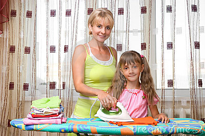 Mother and daughter is ironing