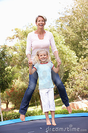 Mother And Daughter Jumping On Trampoline In Garde