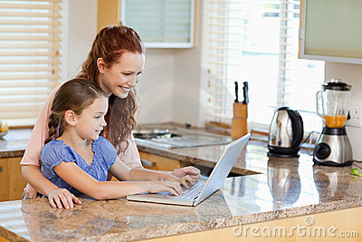 Mother and daughter with laptop in the kitchen