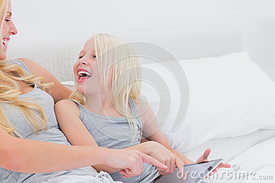 Mother and daughter laughing while using a tablet