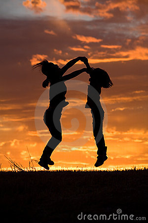Mother and daughter leap at sunset.