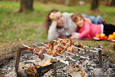 Mother and daughter lie near campfire with grill