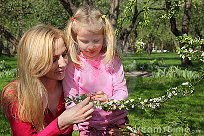 Mother and daughter look at blossoming branch