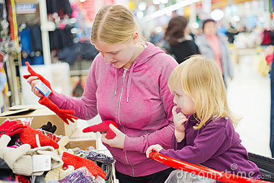 Mother and daughter look gloves in supermarket.