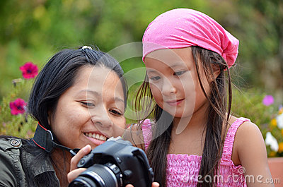 Mother and daughter looking at pictures on camera