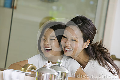Mother And Daughter Looking At Reflection In Bathroom Mirror