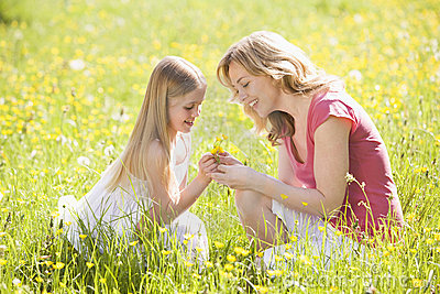 Mother and daughter outdoors holding flower