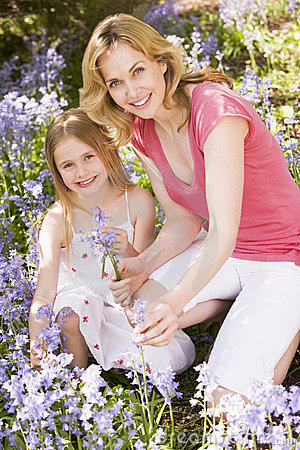 Mother and daughter outdoors holding flowers