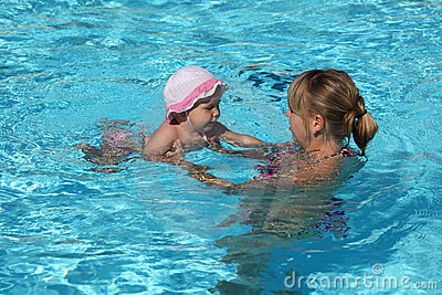 Mother with daughter in a pool