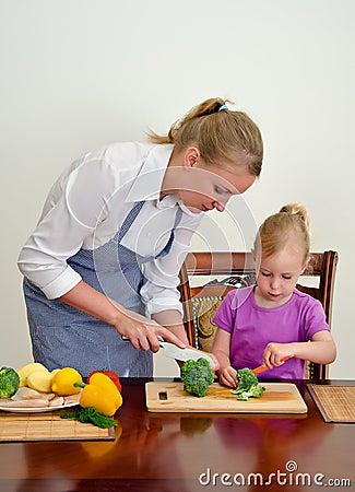 Mother and daughter preparing food.