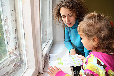 Mother with daughter read history near window