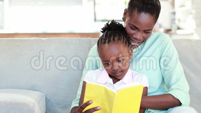 Mother and daughter reading a book. At home stock video