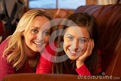 Mother And Daughter Relaxing On Sofa Together