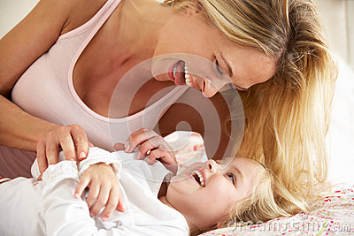 Mother And Daughter Relaxing Together In Bed