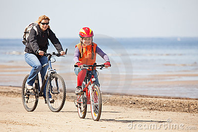 Mother and daughter riding on bicycles