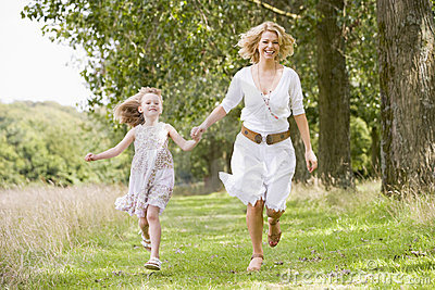 Mother and daughter running on woodland path