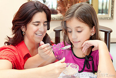 Mother and daughter sharing a dessert
