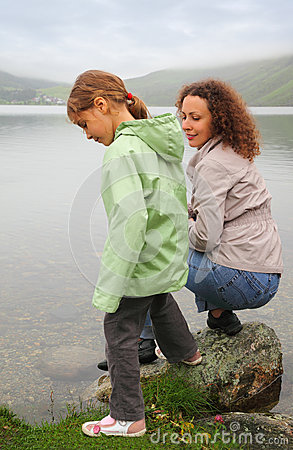 Mother with daughter sit at background of lake