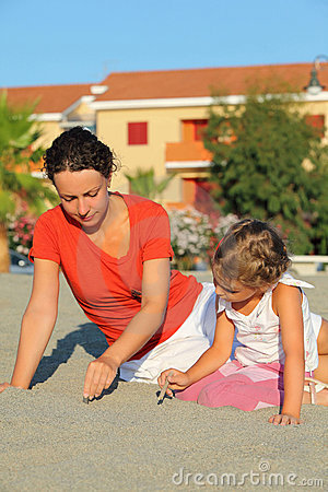 Mother with daughter sit on beach and draw on sand