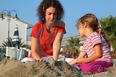 Mother with daughter sit on beach and play