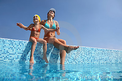 Mother with daughter sit on parapet of pool
