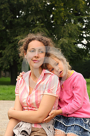 Mother and daughter sit in park