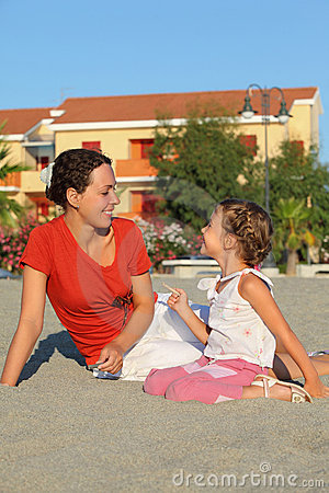 Mother with daughter sit on sand and laugh