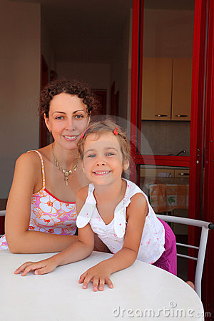 Mother with daughter sit on verandah near table