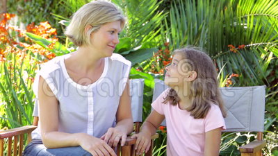 Mother And Daughter Sitting In Garden Chairs And Talking. Mother and daughter sitting in garden chairs talking to one another.Shot on Canon 5D MkII at 25fps stock footage