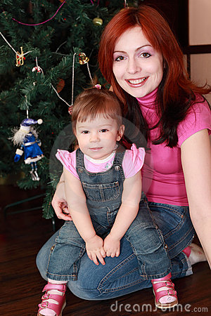 Mother and daughter sitting near christmas tree