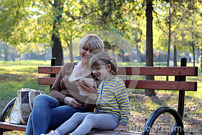Mother and daughter sitting in park