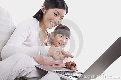 Mother and daughter smiling and sitting close together on the sofa, using and pointing at the laptop, tilt