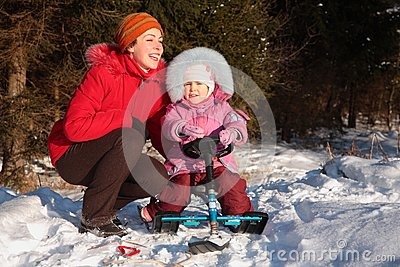 Mother and daughter with snow scooter