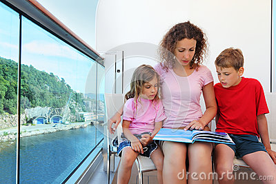 Mother, daughter and son carefully review book