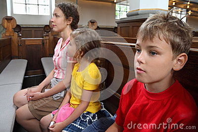 Mother, daughter and son sit on bench in Church