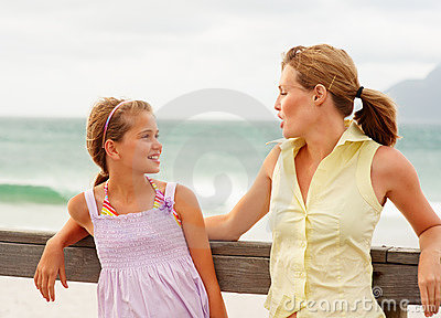 Mother and daughter speaking by a wooden railing