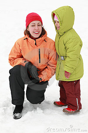 Mother with daughter stand on to snow and laugh